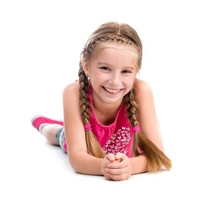 Foto de smiling little girl lying on the floor isolated on white background - Imagen libre de derechos