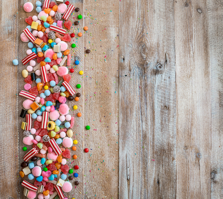 Photo for variety of candies on a wooden background with space for text - Royalty Free Image