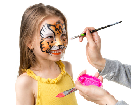 Photo for joyful little girl getting her face painted like tiger by artist - Royalty Free Image