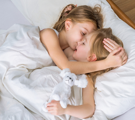 Photo for two little sisters hugging in bed - Royalty Free Image