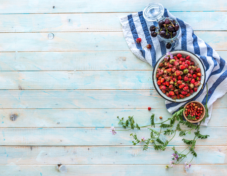 Photo pour Scattered wild flowers, cherries and ripe strawberries, topview - image libre de droit