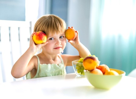 Photo pour cute little girl with peaches in hands at the table - image libre de droit