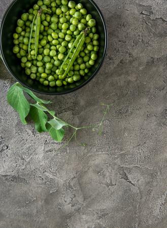 Photo pour Black bowl with freshly harvested green peas, some shells, textured background, topview, copyspace - image libre de droit