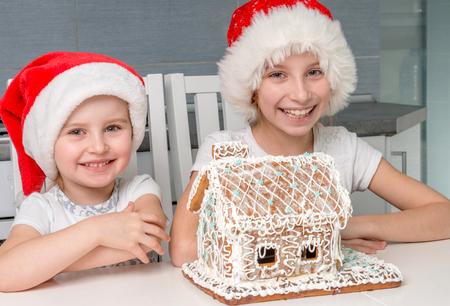 Foto de two smiling sisters in santa hat with creamy biscuit house - Imagen libre de derechos