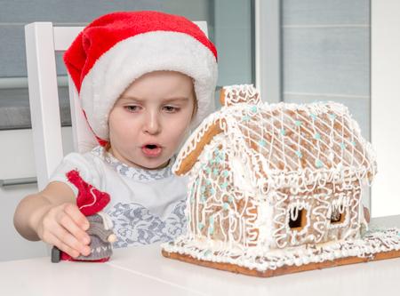 Foto de cute little girl toy near biscuit house - Imagen libre de derechos