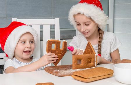 Foto de two little sisters in santa hat making biscuit house - Imagen libre de derechos