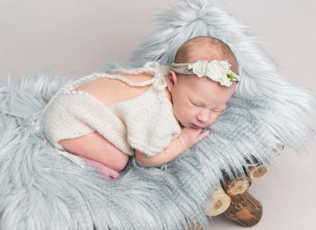Photo pour Newborn baby girl sleeps on small wooden crib. - image libre de droit