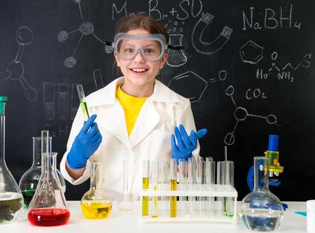 Foto de schoolgirl in white gown doing experiments with liquids - Imagen libre de derechos