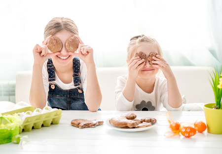 Photo pour Happy little girls holding Easter cookies in front of their eyes - image libre de droit