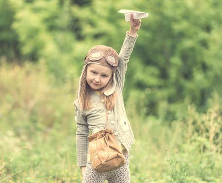 Photo pour cute little girl in helmet pilot with paper airplane - image libre de droit
