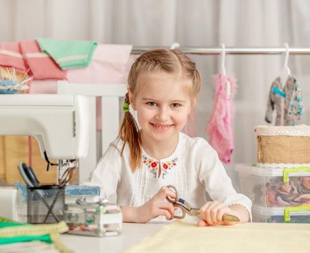 Foto de little girl in a sewing workshop - Imagen libre de derechos
