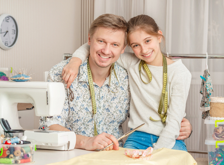 Foto de little girl and her dad in a sewing workshop - Imagen libre de derechos