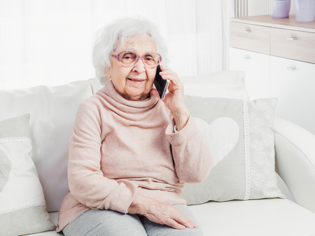Photo for Great-grandmother talking by smartphone - Royalty Free Image