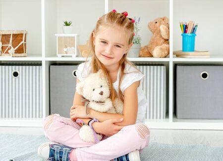 Foto de Little girl hugging teddy bear - Imagen libre de derechos