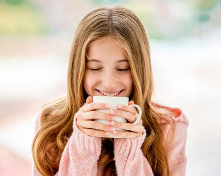 Foto de Sweet girl drinking from cup - Imagen libre de derechos