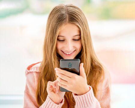 Foto de Teenage girl typing on mobile phone - Imagen libre de derechos