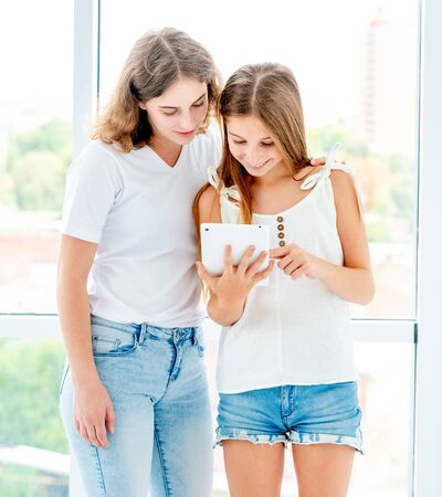 Foto de Girls looking at tablet standing near window - Imagen libre de derechos