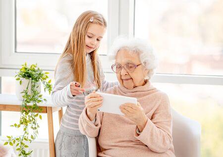 Photo pour Cute girl helping old lady - image libre de droit