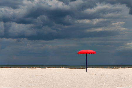 One red parasol on a sandy beach against a stormy sky background.