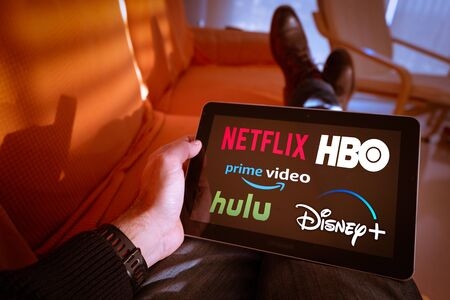 Photo for Barcelona, Spain. January 2019: Man holds a tablet with Netflix, hulu, amazon video, HBO and Disney  logos on screen - Royalty Free Image