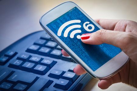Foto de Girl using a smartphone with new wifi 6 on the screen. - Imagen libre de derechos