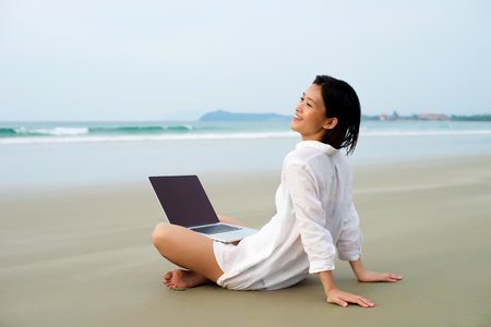 Photo pour Happy girl sitting with laptop working at the beach - image libre de droit