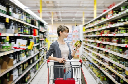 Photo pour pretty woman with a cart shopping and choosing goods at the supermarket - image libre de droit