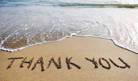Foto de thank you words written on the sand of the beach - Imagen libre de derechos