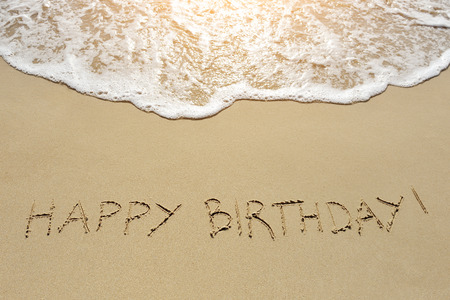 Foto de happy birthday written on the sand beach - Imagen libre de derechos