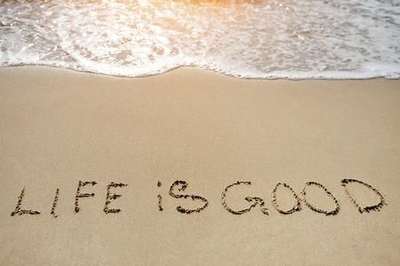 Foto de life in good written on the sand beach - positive thinking concept - Imagen libre de derechos