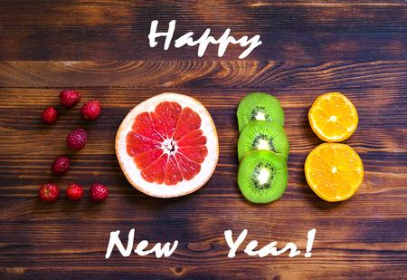 Foto de happy new year 2018 of fruit and berries on wooden background. - Imagen libre de derechos