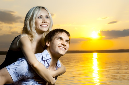 horizontal photo the very happy  sexy pretty couple,  smile, outdoor on sunset or sunrise