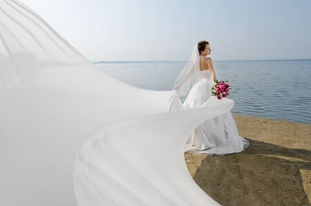 Photo for beautiful fiancee in white wedding dress and big long white train, stand on shore sea - Royalty Free Image
