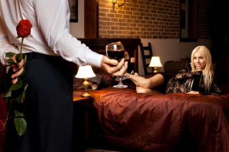 Photo pour romantic evening date in hotel room, guy with  sexy girl on bed - image libre de droit