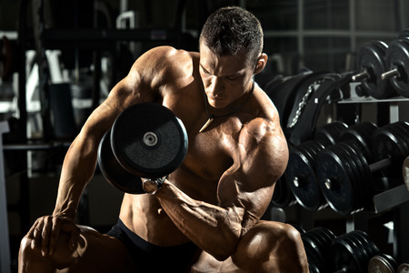 Photo pour very power athletic guy bodybuilder ,  execute exercise with  dumbbells, in dark gym - image libre de droit