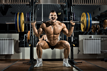 Foto de very brawny guy bodybuilder ,  execute exercise squatting with weight, in gym - Imagen libre de derechos