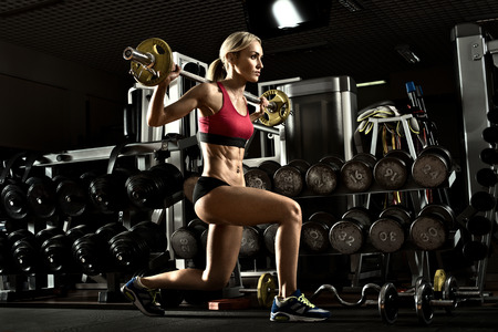 Foto de Beautiful girl bodybuilder ,  execute exercise with  dumbbells, in dark gym - Imagen libre de derechos