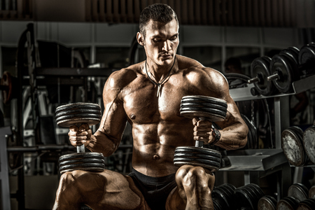 Foto de very power athletic guy bodybuilder , sit with  dumbbells, in dark gym - Imagen libre de derechos