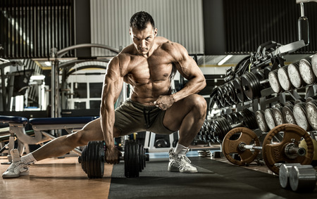 Foto de bodybuilder man, execute exercise with  dumbbells, inside gym, horizontal photo - Imagen libre de derechos