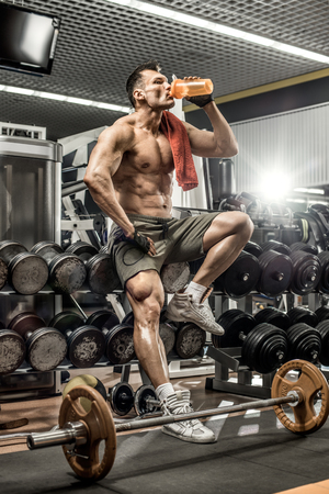 Foto de guy bodybuilder tired sit in gym and drink sportive nutrition - protein of shaker , vertical photo - Imagen libre de derechos