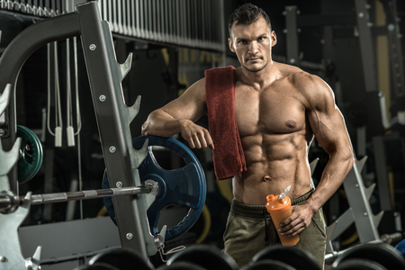 Foto de guy bodybuilder tired in gym hold shaker with sportive nutrition - protein of shaker , vertical photo - Imagen libre de derechos