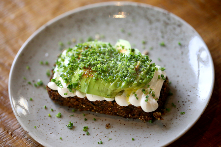 Photo for Macro photo of delicious wholesome toast with avocado on a plate in a restaurant - Royalty Free Image