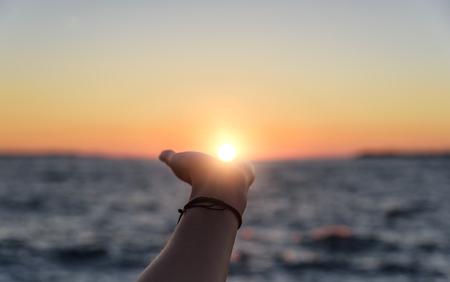 Foto de Hand reaches for the sun at sunset. - Imagen libre de derechos