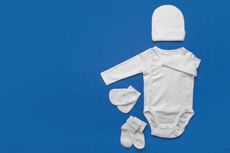 Photo pour Set of white baby clothes on blue background. - image libre de droit