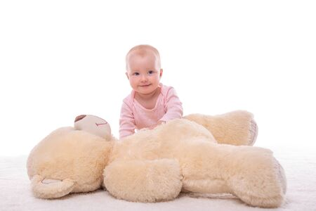 Foto de Little girl and a plush bear on a white background. - Imagen libre de derechos