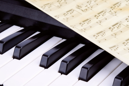 Photo pour octave, piano keys closeup. sheet with notes lying on top of the piano - image libre de droit
