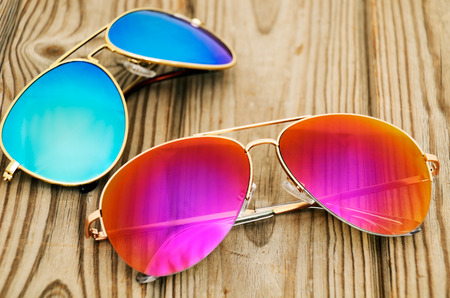 Foto de two colored sunglasses on the wooden background. horizontal - Imagen libre de derechos