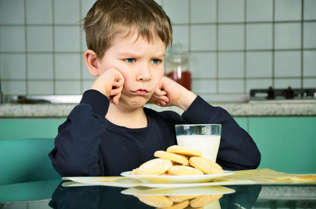 Photo for Angry little boy sitting at the dinner table. biscuits on the table and a glass of milk. the boy did not want to eat the food. green and gray kitchen furniture in the background. horizontal - Royalty Free Image