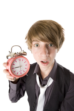 Photo for A geeky teen holding an alarm clock and late for a date. - Royalty Free Image