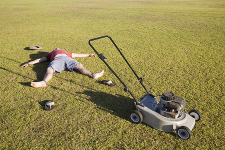 Foto de An exhausted man lying on the ground collapsed after mowing a huge lawn. - Imagen libre de derechos